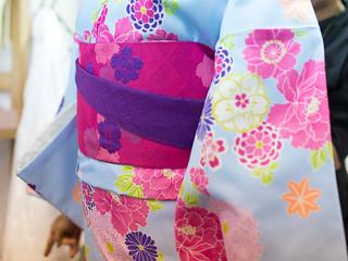 Young woman tiing sash on Kimono