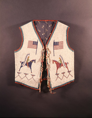 Lakota Vest. Buckskin, solidly beaded, four Indians in war bonnets on horseback and with U.S. flags on white ground.  Blue beaded band border. Lined with figured dark cotton and buried with red. Thong ties. For larger image of vest, see T4-495.