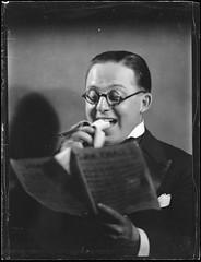 Man [Eric Sheldon?] eating banana and reading sheet music