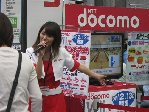 A Bic Camera employee demoing Wii Sports outside the store.