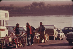 Flea Market Tables Lined Up at White Cloud, Kansas, near Troy, in the Northwest Corner of the State...09/1974 (The U.S. National Archives) Tags: road men water river women market tables kansas trucks fleamarket environmentalprotectionagency documerica usnationalarchives nara:arcid=557130