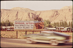 photo by David Hiser large sign of 'Mr. Manufacturer: Moab, Utah has space for you and your plant too' and a car speeding past