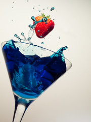 Another flying strawberry.. (david.kittos) Tags: blue red white glass fruit strawberry martini splash highspeedphotography zd 50mmmacro20 strobist lightscience flyingstrawberry strobistsundays