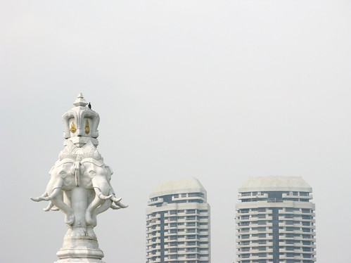 White statue and buildings disappear against the hazy sky - Bangkok, Thailand