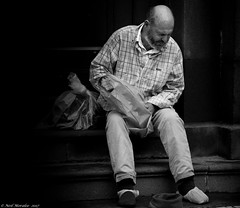 2 shirts, no shoes. (Neil. Moralee) Tags: man old mature homeless poor destitute alone street candid tramp vagrent black white blackandwhite bw bandw mono monochrome funchal unemployed poverty refuge rough sleeping sleepingrough bald balding shoes shirts plastic bag plasticbag feet wet wetfeet steps sitting outdoor people dark controversial hidden secret neil moralee nikon d7100