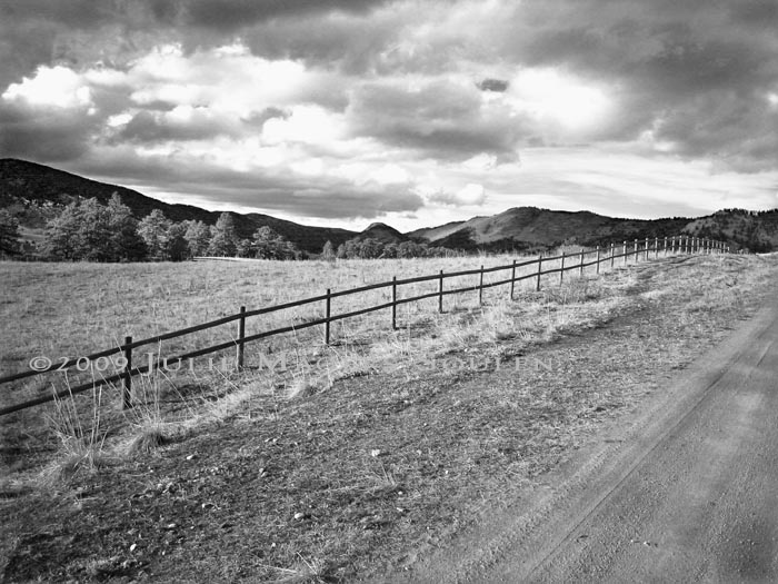 black and white photo of western fence line and valley view in Colorado