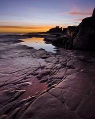 Doleritic Grooves, Bamburgh; Northumberland (Corica) Tags: sunset sky seascape castle sunrise nikon rocks northumberland northsea grooves bamburgh d300 landcsape dolerite corica