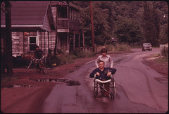 Jack Smith, 42, a Disabled Miner in Rhodell, West Virginia, Is Wheeled Down the Street by His Daughter, Donna, 16, to the Beer Joint He Operates 06/1974