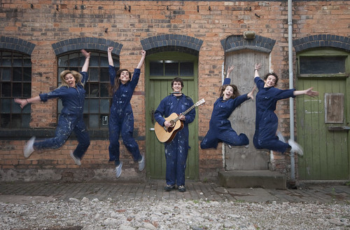 Five people from Tin Box Theatre Company jumping in the air excitedly
