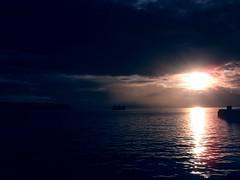 Seattle Pier and Ferry (hiimniko) Tags: seattle sunset sun mountains water rain ferry clouds dark bay pier dock break sound elliott puget