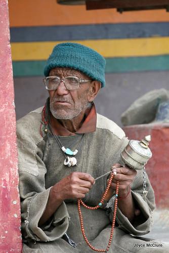 Elderly Ladakhi man holding prayer wheel and wearing traditional costume