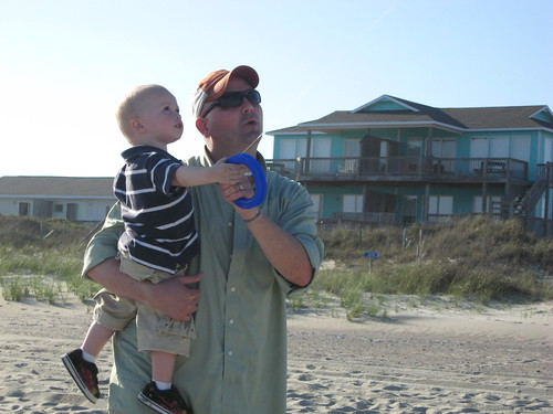 Brandus holding two year old Voldemort, both looking up and flying a kite