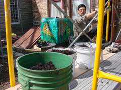 Future Green owner Swee Sim climbs onto the scaffolding to load buckets of soil for his rooftop garden May 4. ~photo Michael Timm