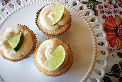 3 lime cupcakes on a white cake plate