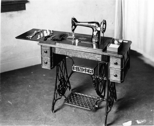 Treadle sewing machine with display of sewing equipment on arm. No date given, but ...