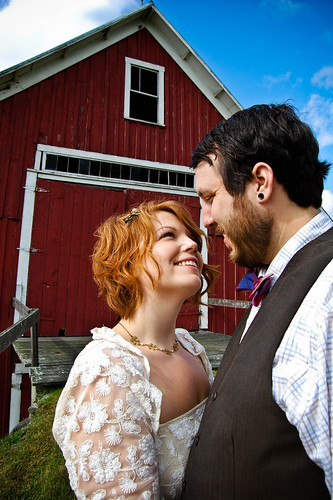 bride and groom in front of barn