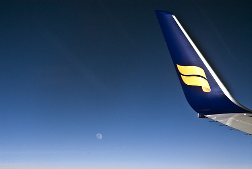 tail of Icelandair plane, the moon and blue sky by jackie weisberg.