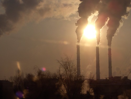 smokestacks emitting pollution backdropped against sun