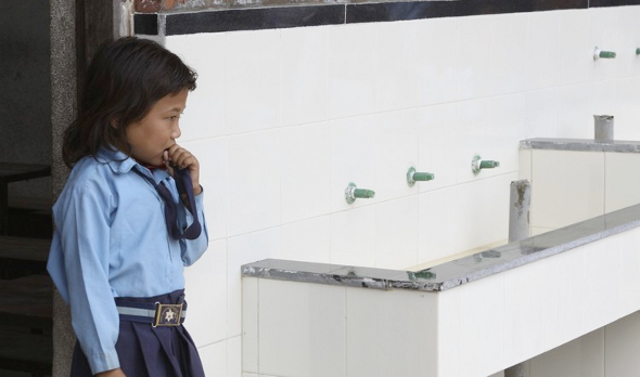 A student patiently waits for our clean drinking water station to be completed