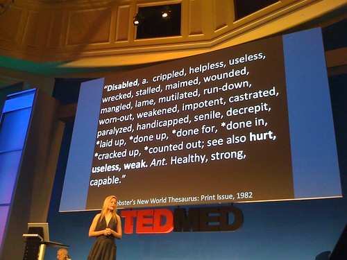 Aimee Mullins gives a TED talk, standing in front of slide which highlights the popular negative connotations which go with the term disabled - showing the synonyms listed in a thesaurus