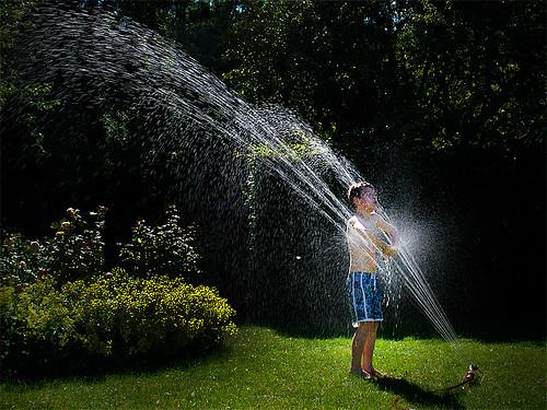 Axel tar ett svalkande dopp i vattenspridarens stråle