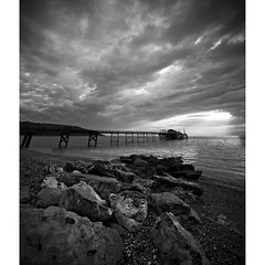 Totland Rocks (s0ulsurfing) Tags: ocean light shadow sea sky blackandwhite bw cloud sunlight white seascape black texture tourism beach water lines weather silhouette rock clouds composition contrast landscape island grey mono evening bay coast pier vanishingpoint seaside twilight rocks skies patterns jetty wide shoreline may silhouettes dramatic wideangle monotone x coastal shore vectis isleofwight vista coastline ripples drama landschaft isle 2009 wight 10mm converging totland sigma1020 totlandbay s0ulsurfing aplusphoto totlandpier infinestyle vertorama