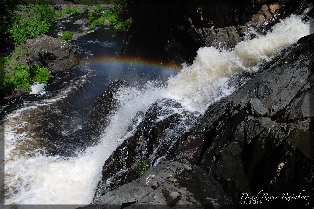 A view from the top of a rocky waterfall, looking downstream, with a rainbow visible in the mist from the fall.