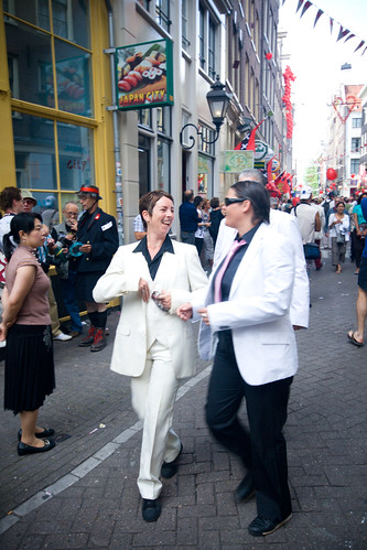 Two people in white suits walking down a busy street, smiling and laughing together.
