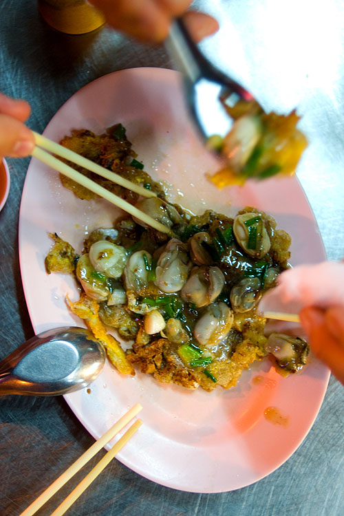 Digging into or lua, a crispy egg batter topped with oysters, Nay Mong, Bangkok's Chinatown