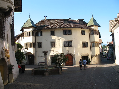 Steinbrunnen mit historischem Gebäude im Ortskern von Kaltern