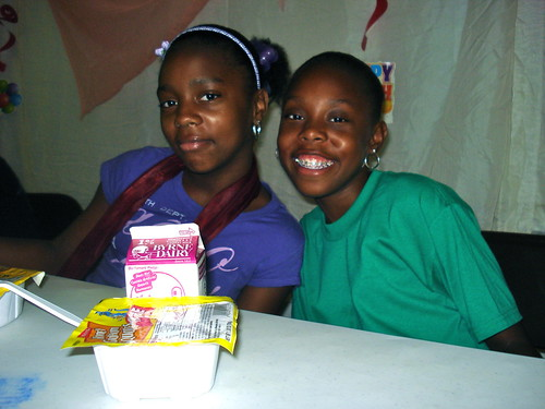 Jade Davis, left, and Keilazia Marshall, right, both 11, enjoy a breakfast at Greater New Testament Missionary Baptist Church before starting the day's activities.