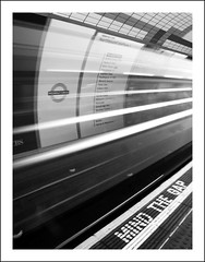 Mind the Gap [Tube Motion 1/3] (Photolab.AJ) Tags: street city bw white motion black blur london station wall speed train underground logo wagon lights bill moving boards focus baker metro circus centre north tube platform zug piccadilly trains center headlights line rush u londres rails arrival northern bound bahn zwart wit centrum adds reklame entering trein halte londen muur northbound lampen tegel beweging sporen timing gleis halt snelheid onscherp koplampen lichten rijtuig aankomst oxfort mind cmwdblackandwhite canong9 photolabaj cmwdweeklywinner gap binnenrijden imga6907fljpg tubemotion