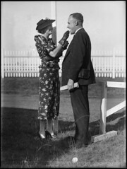Man and woman at Warwick Farm racecourse (Powerhouse Museum Collection) Tags: two people blackandwhite woman man smile hat fashion standing outdoors happy couple feeding carinho smiles australia clothes event gloves icecream sorriso australien racecourse vestido powerhousemuseum luvas thomaslennon rennbahn pferderennbahn warwickfarm tomlennon xmlns:dc=httppurlorgdcelements11 mouthinspection dc:identifier=httpwwwpowerhousemuseumcomcollectiondatabaseirn388521 warwickfarmracecourse thomastrembathlennon