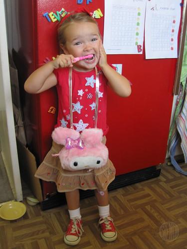 posing next to her tooth-brushing chart
