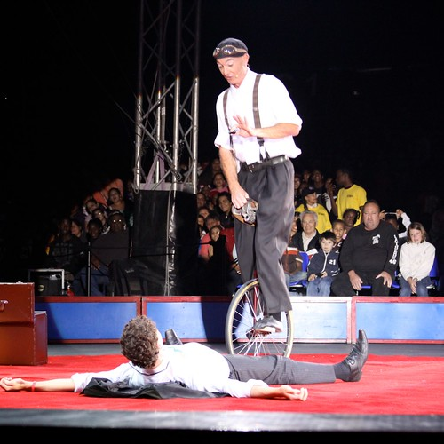 Justin Case Performing Unicycle Hop with Volunteer Nathan Bliss. Photo © Maya Haddad via flickr