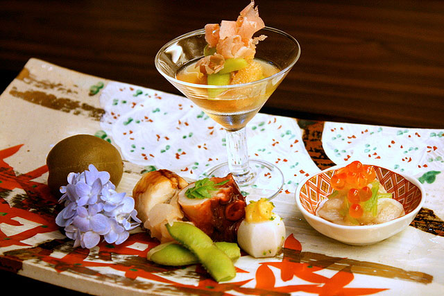 Appetiser platter - kazunoko (in glass), aoume or Japanese plum, anago (sea eel) sushi, tako, zuiki (stem of taro) with ikura (salmon roe), yam with miso, edamame beans