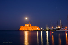 Full moon over the lighthouse (esther**) Tags: blue light red sea sky orange moon lighthouse reflection colors beautiful yellow night boats island gold view greece moonrise rhodes interestingness218 interestingness176