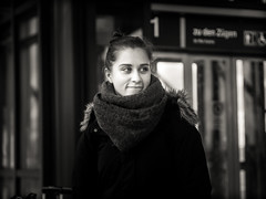 candid.portrait.(train.station.girl) (grizzleur) Tags: girl beautiful smile coy shy pretty young woman lady scarf bw mono monochrome street photography portrait candid candidportrait olympusomdem10mkii olympusmzuiko45mmf18 olympus olympusstreetphotography