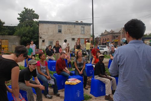 Participants listen to a presentation by CUP while using recycling bins as chairs. The 70 bins would later be distributed in the neighborhood.