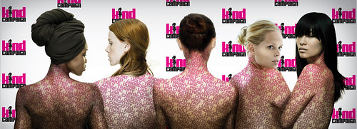 "Five women stand with their bare backs facing the camera, against a background pattern of tiny Kind Campaign logos. The first has dark skin and her hair is wrapped in a black scarf. The next three have light skin and red, brown and blonde hair, respectively. All three have long hair, but the redhead's is down and the brunette's and blonde's are in buns. The last woman is the only one looking directly at the camera. She has a still expression, a medium skin tone and untied long black hair with bangs. Across their backs, insults are projected in pink capital letters: ""FAKE"", ""TRASHY"", ""UNTRUSTWORTHY"" and more."