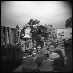 ten dollar hat (QsySue) Tags: blackandwhite hat sign mediumformat toycamera hats 120film orangecounty vignetting fleamarket huntingtonbeach swapmeet goldenwest expiredfilm holga120n tendollars developedathome agfafilm reallyoldfilm like30yearsold