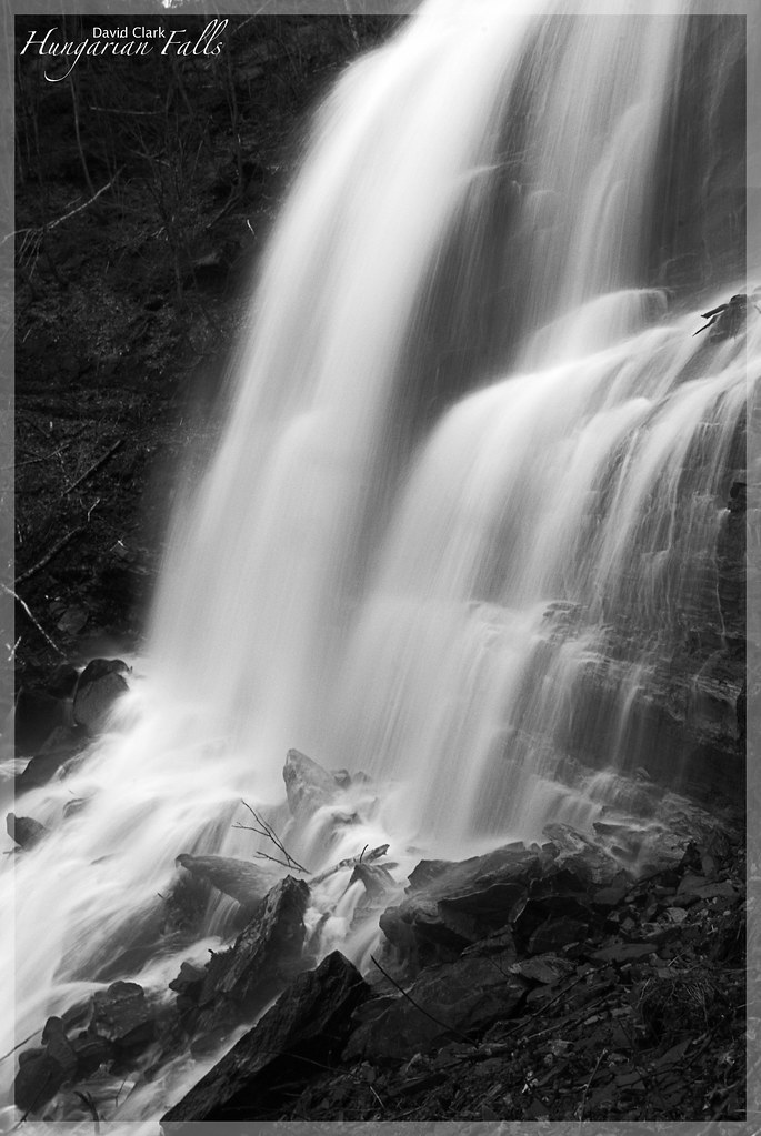 A close up side view of a cascading waterfall, with sandstone rock, in black and white.
