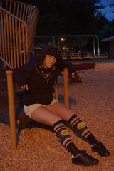 Are we going to play? (Fearless Zombie) Tags: park summer woman black sexy girl hat playground yellow socks lady night hoodie streetlight sitting play bark blonde shorts childish tomboy smileyface kneehigh skatershoes