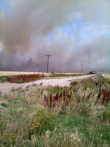 A combine prepares to dump in midst of the fire