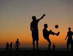 Greek Football (timsauder) Tags: boy sunset red sea orange mountain man men beach boys grass silhouette youth walking greek evening football kick soccer side young player greece shore fist kicks plays players kicker stance patras clenched  hells    timsauder patrae ptra ptrai