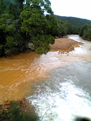 Yellow tailings water mixing with black tannin water beside ABT railway