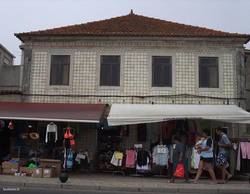Uma casa antiga toda coberta de azulejos, com a sua loja no rés-do-chão