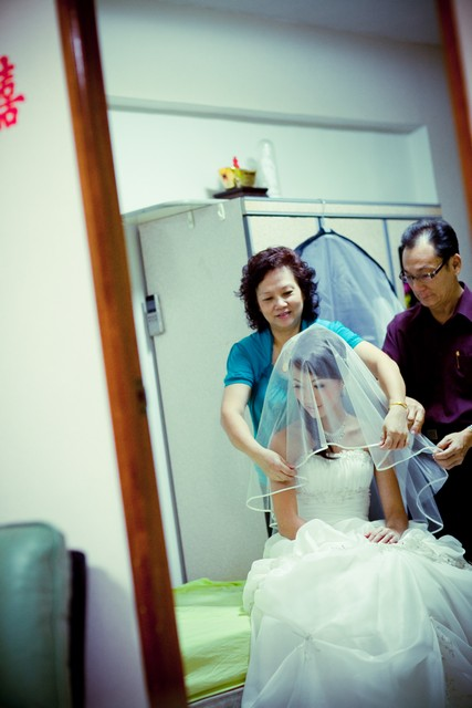 bride putting on veil with parents