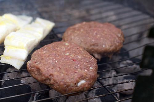 Når du legger de rå hamburgerne på grillen er det lurt å passe på at de ikke setter seg helt fast.