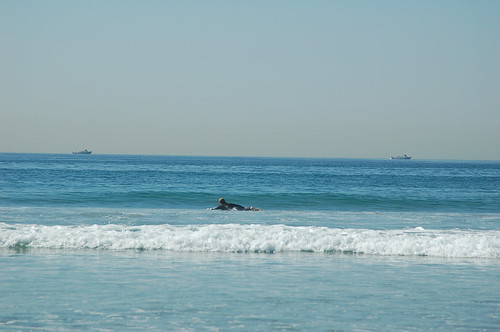 One surfer and two naval ships in the waters off San Diego